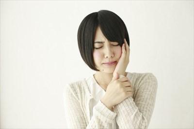 虫歯を手で押さえる女性